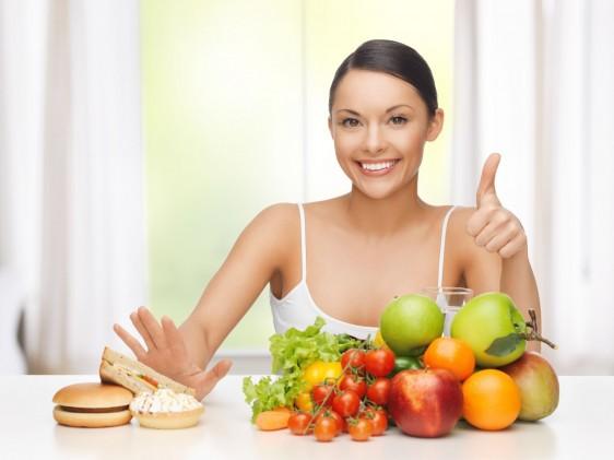 Mujer rechazando con la mano derecha comida rápida enfrente tiene frutas y con la mano izquierda levanta el dedo pulgar