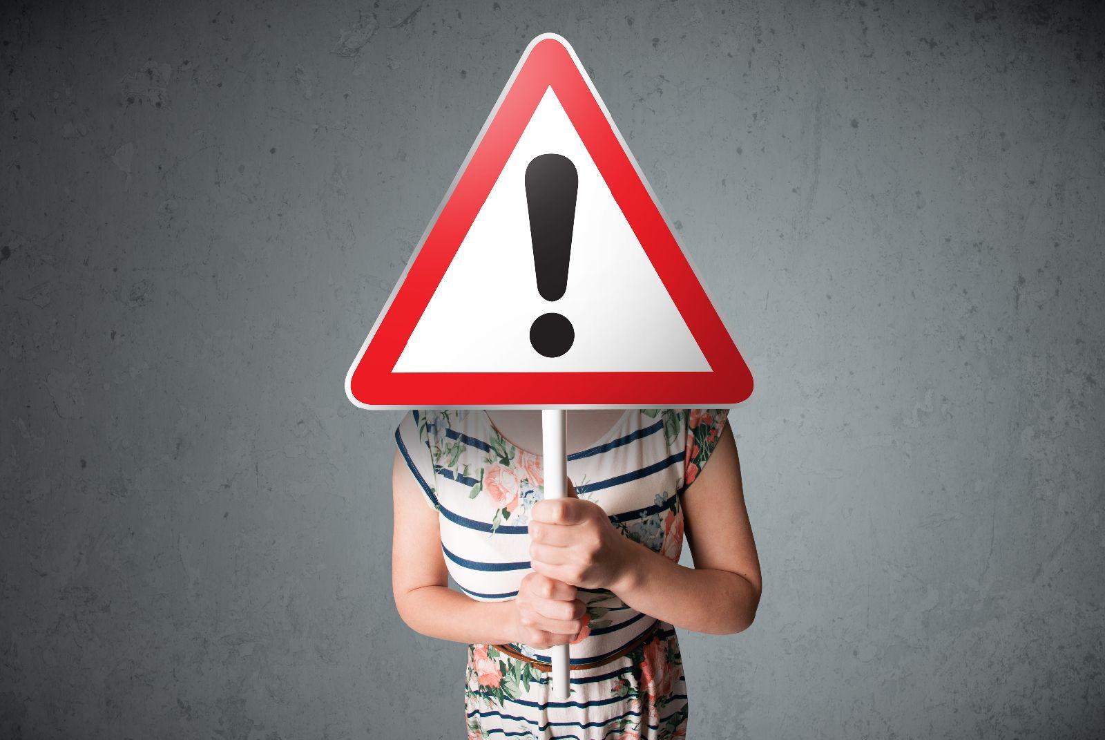 Mujer jóven esconde su rostro detrpas de un anuncio que tien un signo de exclamación en la mano