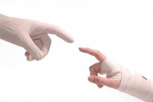 Mano con guantes de latex (médico) tocando a mano con vendas (paciente)