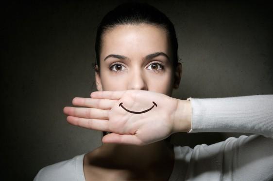 Mujer tapandose la boca con la mano, en la mano tiene sibujada una sonrisa