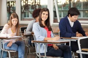 Adolecentes sentados en bancas de una escuela escribiendo