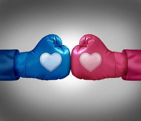 Guante de box azul con un corazón enfrentado a otro guante de ox rosa con un corazón