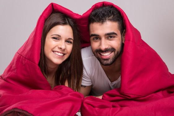 mujer y hombre debajo de ua sabana roja sonriendo
