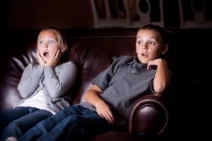 Dos niños observando en la oscuridad una televisión