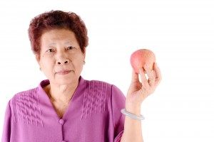 Healthy lifestyle concept. Asian senior woman eating an apple ov