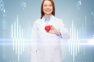 Mujer en bata blanca sonriedo sostiene un corazón al fondo un entorno azul