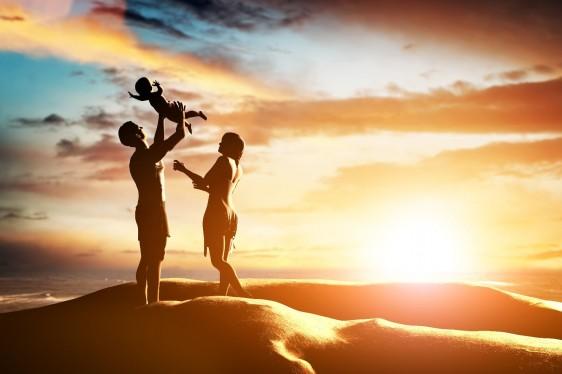 ilustración con silueta de padre sostiene arriba en brazos a niño con mama enfrente atrás un atardecer