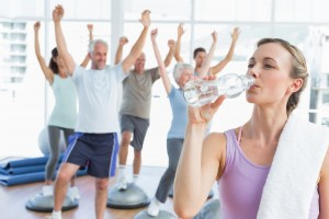 Mujer en ropa deportiva tomando agua de uina botela transparente en el fondo personas haciendo ejercicio