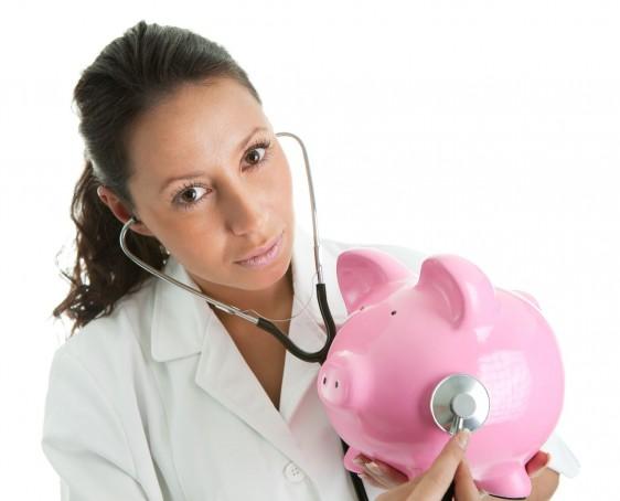 Doctora en bata blanca con estetoscopio escuchando a una alcancía en forma de cochinito rosa