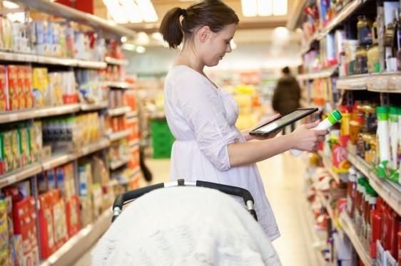 Mujer observando etuiquetas en productos dentro de un anaquel de supermercado
