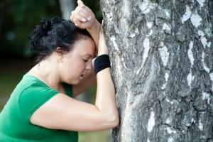 Mujer con obesidad vistiendo ropa deportiva recargándose en un arból cansada
