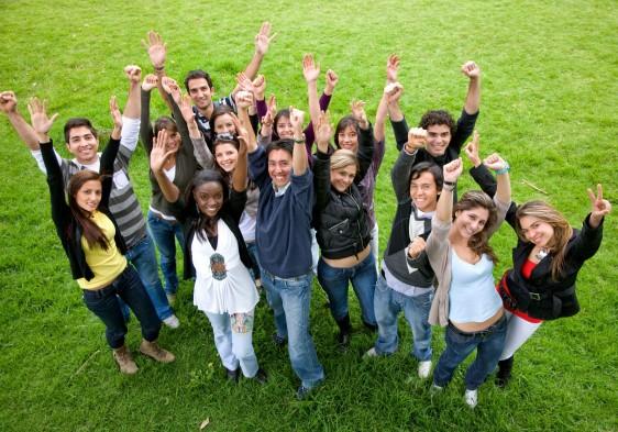 Grupo de jovenes con los brazos arriba en señal de animo
