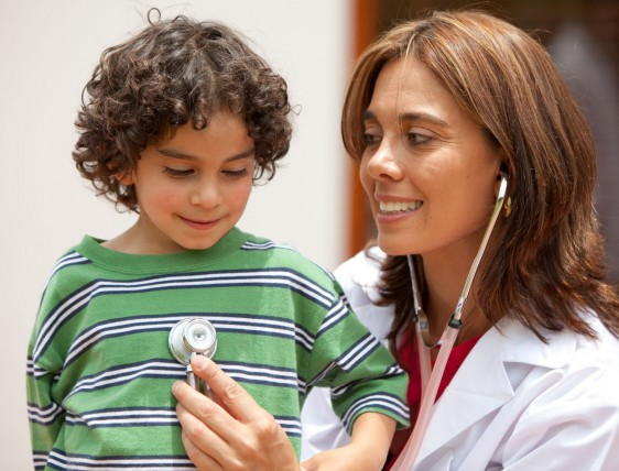 Mujer en bata blanca sontiendo con estetoscopio en la mano que pone en un niño