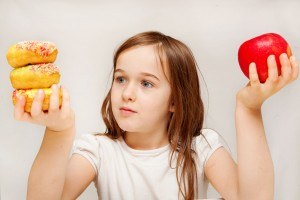 Niña sostiene manzana con su mano derecha y pastel con la izquierda observandolos