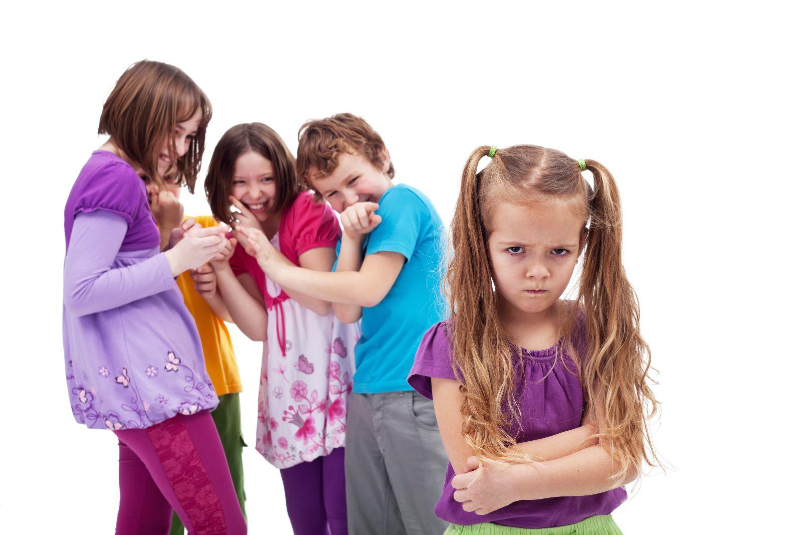 Niña molesta y apenada atras niños burlandose