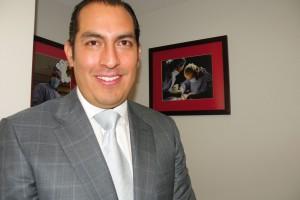 Juan Fernando Calderon Carrillo de traje sonriendo con cuadros de cirugias en la parte posterior