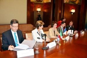 Personas sentasas en mesa de madera al frente banderines de méxico y francia