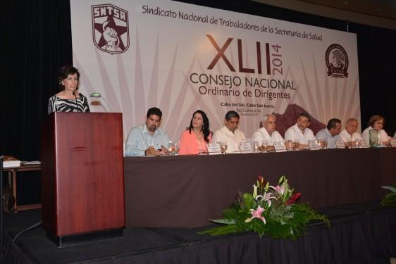 Marcela Velasco González en un podium atras una mesa con personas y un letrero logotipo del XLII consejo nacional ordinario de dirigentes