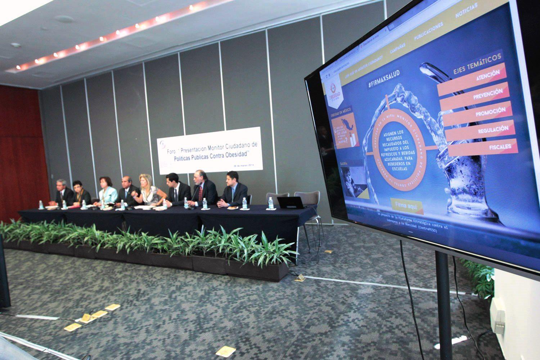 Añ frente una pantalla mostrando el sitio web de Obesidad en la mira, al fondo una mesa con los expositores