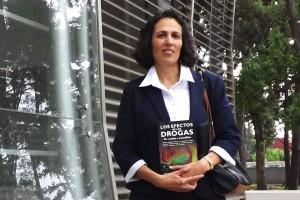 Silvia L. Cruz de pie sosteniendo su libro en las manos