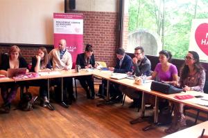 """Personas sentadas en mesa en forma de heradura al fondo logotipos del movimiento """"No Hate speech"""""""