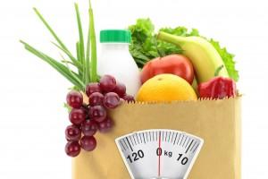 Un bolsa de papel con frutas y verduras, enfrente de la bolsa se simula una bascula
