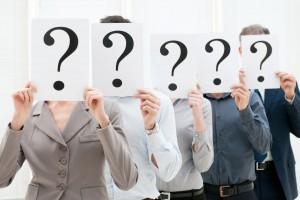 Un grupo de cinco personas con hojas de signos de interrogación
