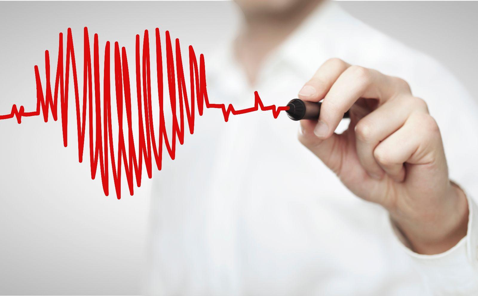 Una persona pinta en un vidrio con plumin rojo un corazón con rayas horizontales que simulan es electrocardigrama