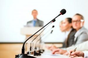 Acercamiento a un microfono de mesa al fondo personas sentad y un podio con una persona borrosa