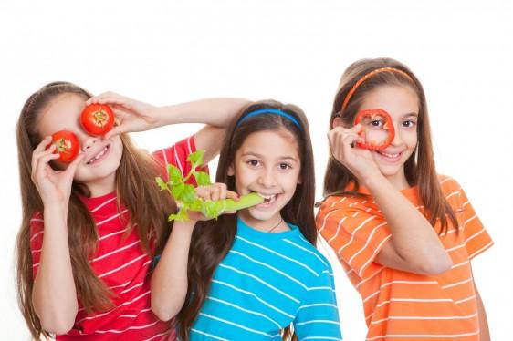 Tres niñas una comiendo veduras y dos jugando con ellas