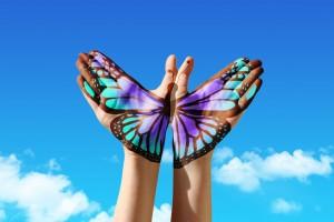 Dos manos con dibujo de mariposa suimulando volar en el cielo