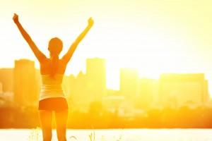Mujer de espalda con los brazos arriba en un amanecer