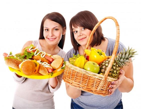 Mujer obesa con canasta de frutas y mujer delgada con comida rápida