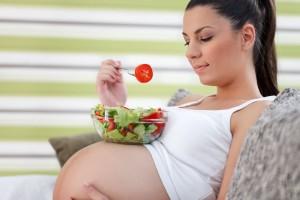 Mujer embarazada sentada con un plato de ensalada