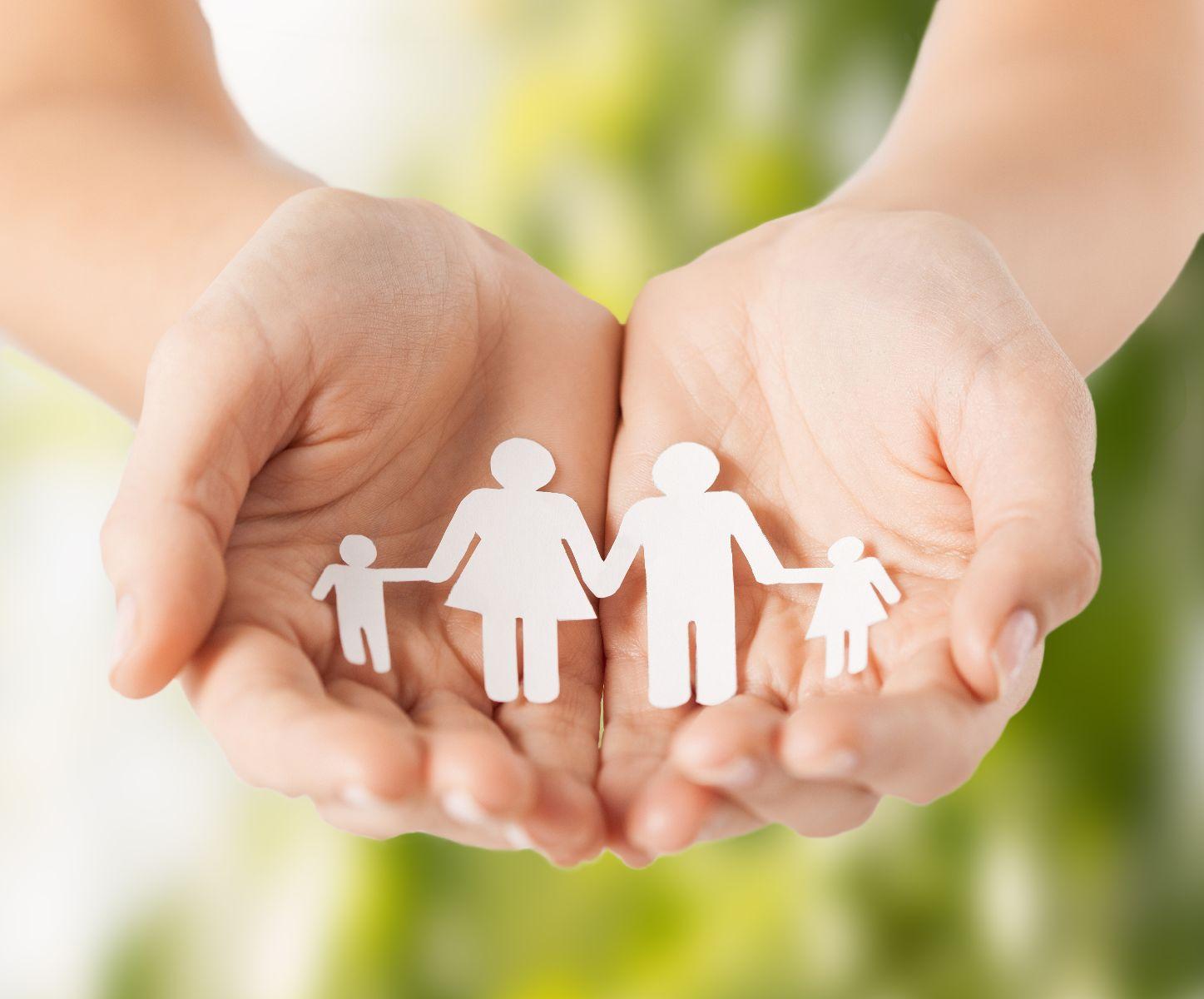 Acercamiento a manos que sostienen un recorte en papel de un ícono de familia