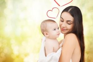 Madre abrazando a bebe con ilustración de corazones arriba de ellos al fondo tonalidades doradas