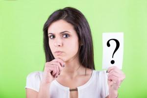 Mujer sosteniendo hoja con signo de interrogación