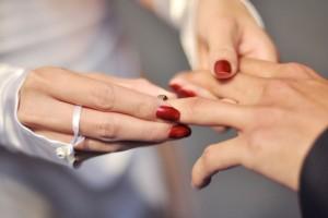 Acercamiento a la mano de un novio cuando la novia le pone un anillo