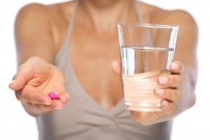 Acercamiento a una mujer que extiende una pildora y un vaso de cristal con agua