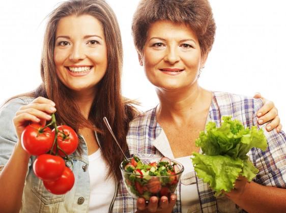 Jóven sostenidndo jotomates y abrazando mujer madura con plato de ensalada en una mano y en la otra hojas de lechuga