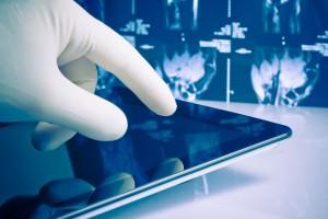 Acercamiento a mano con guante de latex tocano pantalla de compuradora