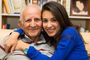 adulto mayor en camisa gris siendo abrazado por joven en camisa azul