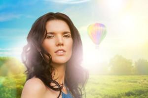 Mujer con vestido azul atras un campo verde con un globo aerostatico y un arcoiris