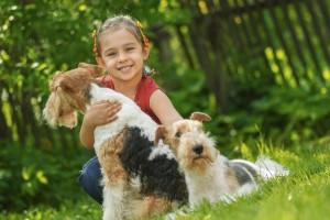 niña en un jardín abrazando a un perro, otro perro se encuentra sentado