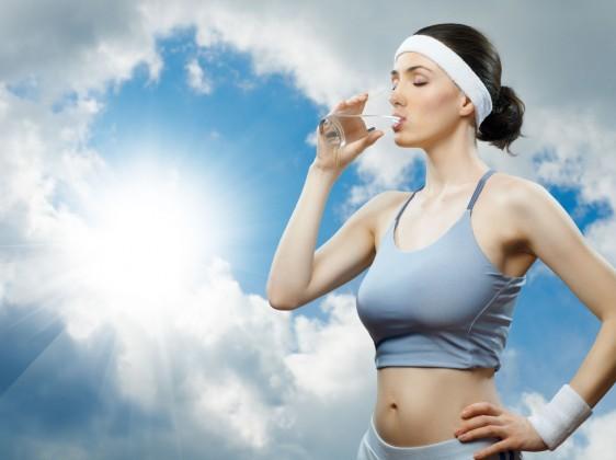 Mujer en ropa deportiva bebiendo agua al fondo un cielo azul y el sol
