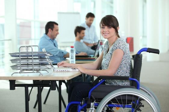 Mujer sentada en silla de ruedas en una oficina trabajando con una computadora al fondo oficinistas trabajando