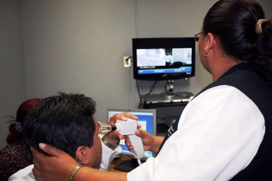 Enfermera con aparato en una mano sentado una persona que observa de cerva el aparato de la enfermera al fondo una pantalla con un instructor