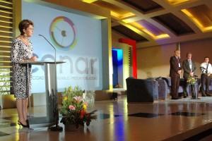 Secretaria de Salud en un podium al fondo el logotipo de CANAR