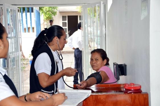 Enfermera tomando la presión a una paciente en una clínica