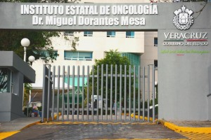 Imagen de la entrada al Instituto Estatal de Oncología de Veracruz, barda gris con el texto de la instutución en la parte superior al fondo un edificio amarillo